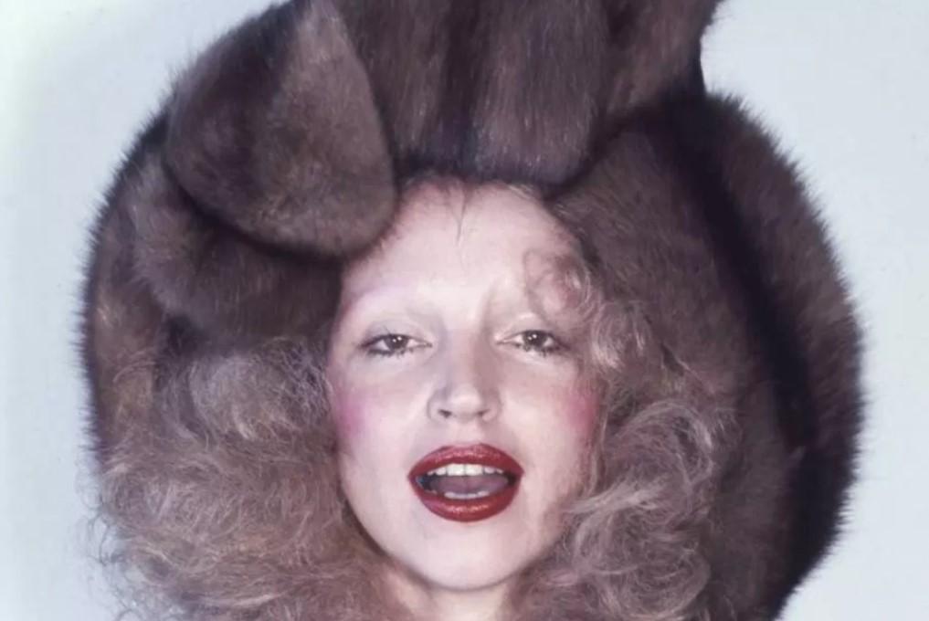 Retrato de Elke Maravilha posando como modelo com batom vermelho e gorro de inverno feito de pele.