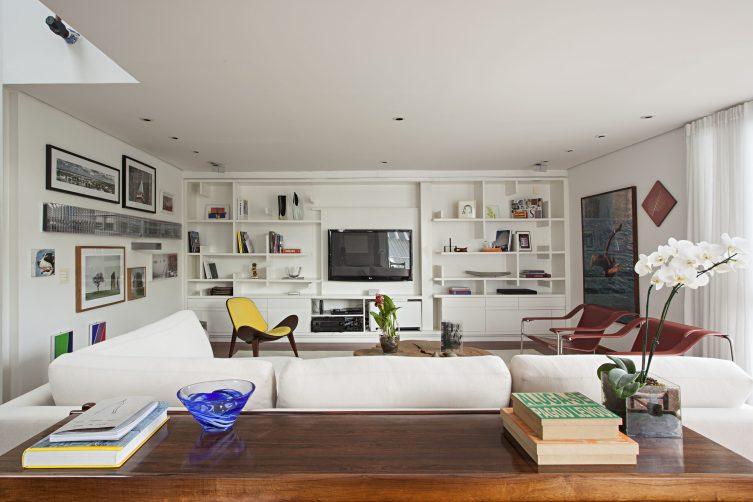 Sala de estar branca com objetos coloridos.