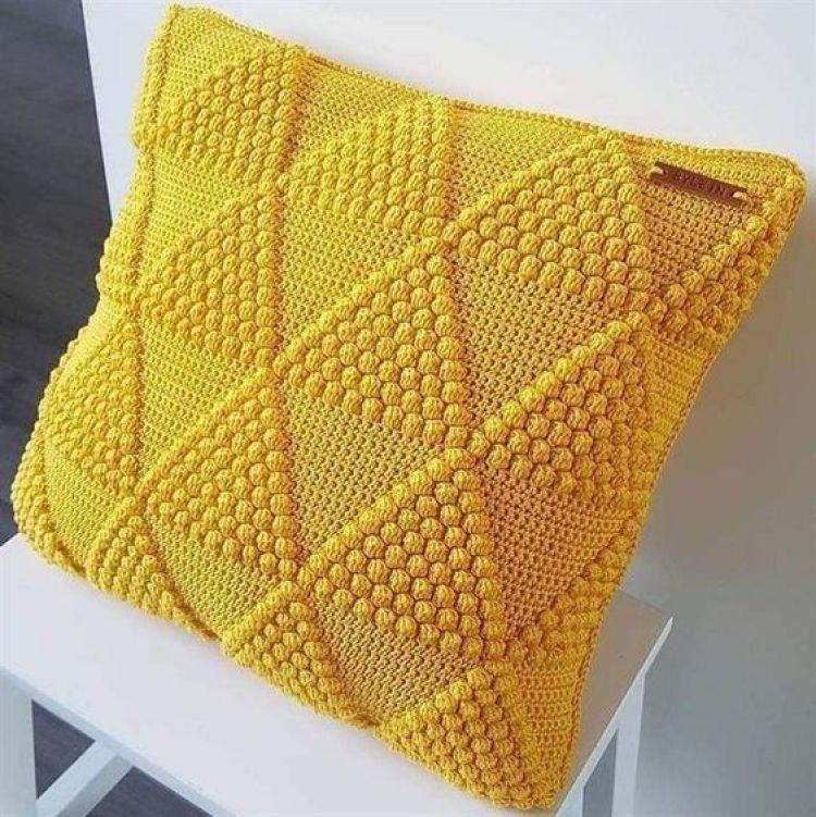 Almofada amarela de crochê.