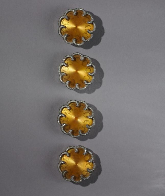Foto de 4 botões douradosde Peter Carl Fabergé em forma de flor em fundo cinza