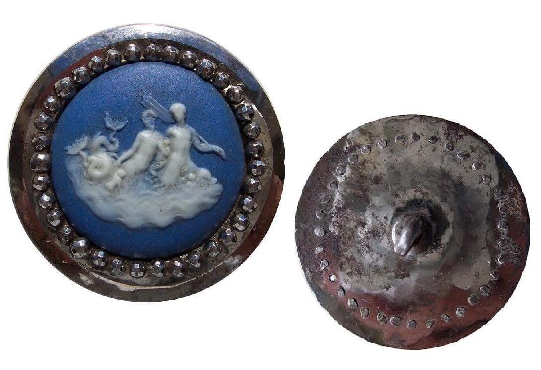 Botão de prata adornado com cerâmica azul e branca com a representação de sereias em fundo branco