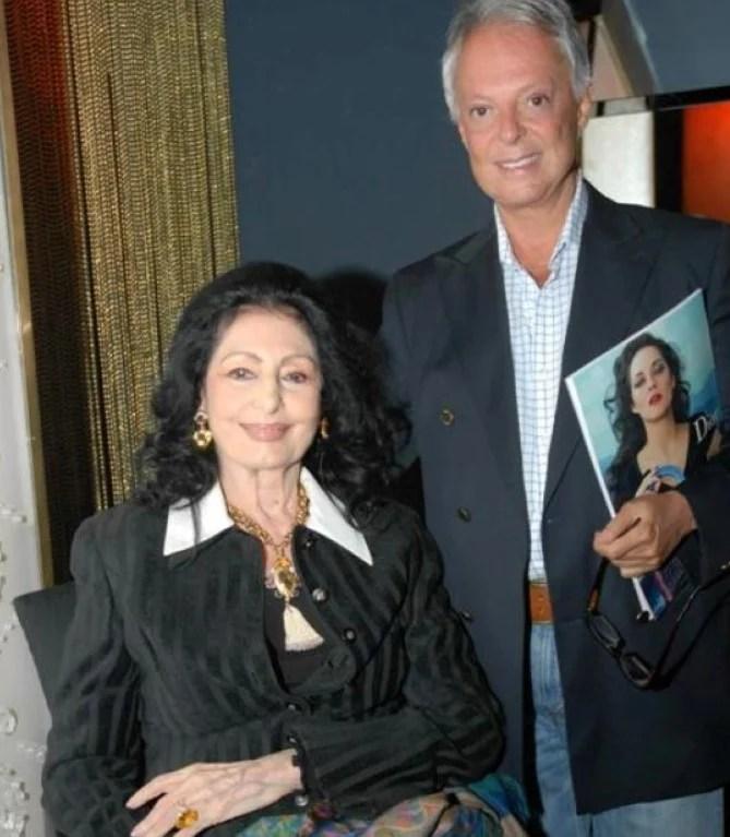 Foto de Carmen Mayrink Veiga e Guilherme Guimarães mais velhos posando lado a lado, ela sentada e ele em pé com um revista