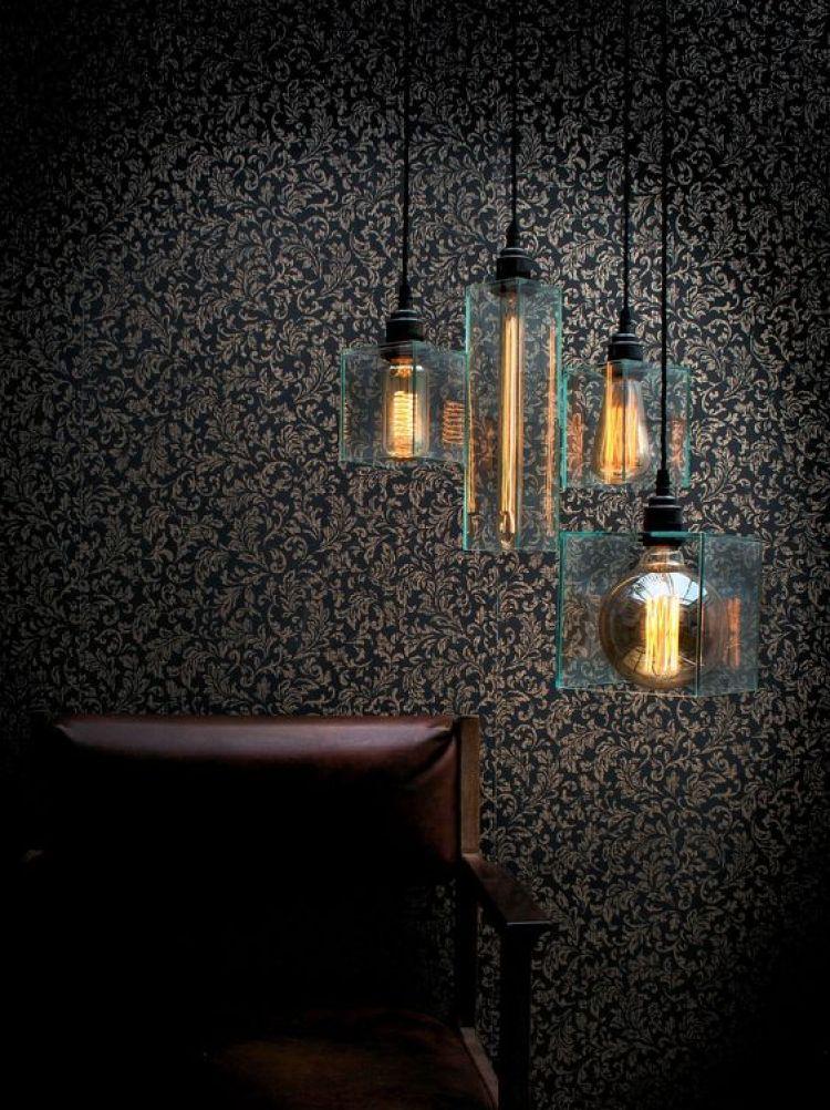 Sala escura com quatro luminárias suspensas.