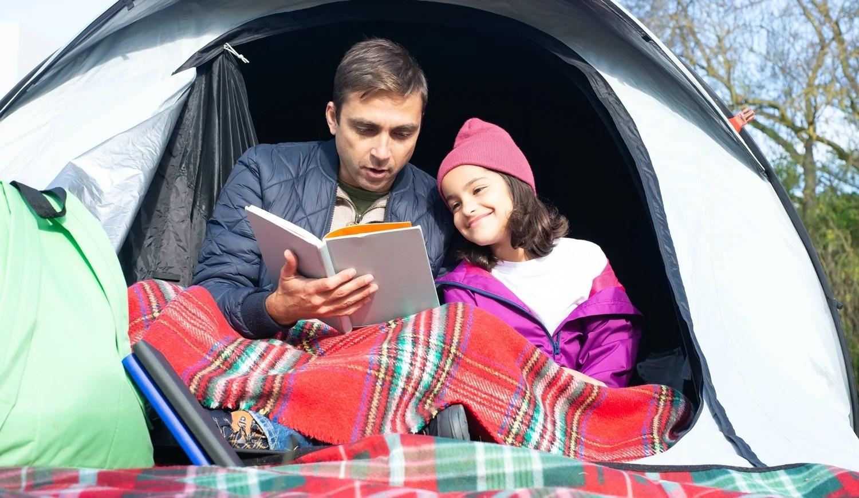 Foto de pai e criança lendo livro.