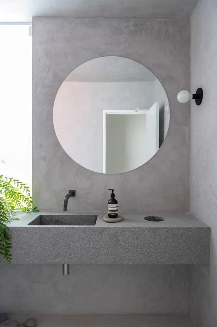 Espelho redondo e parede com efeito cimento queimado.