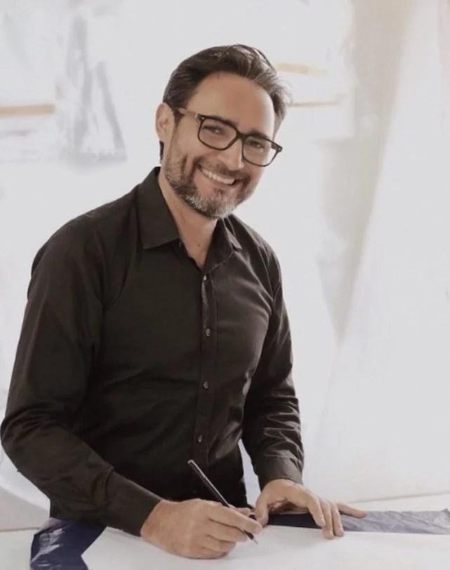 Retrato de Ivanildo Nunes posando sorrindo sentado a desenhar em um papel