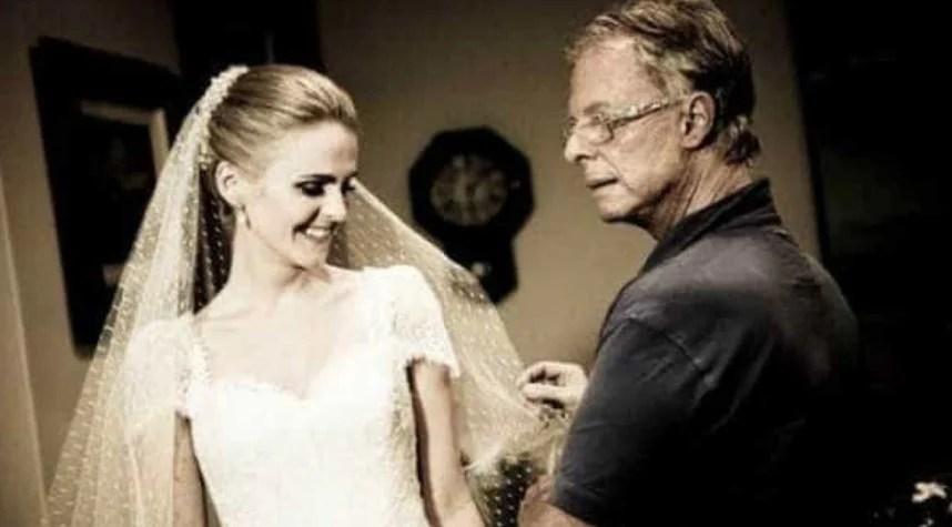 Foto do estilista brasileiro Guilherme Guimarães a segurar o véu de uma modelo vestida de noiva