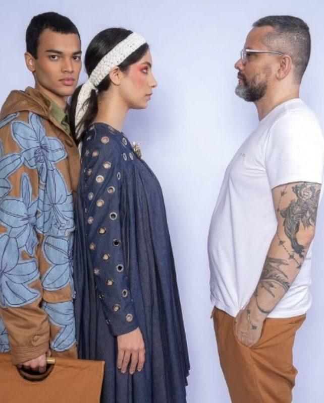 Um casal de modelos posando de perfil encarando o estilista Ronaldo Silvestre
