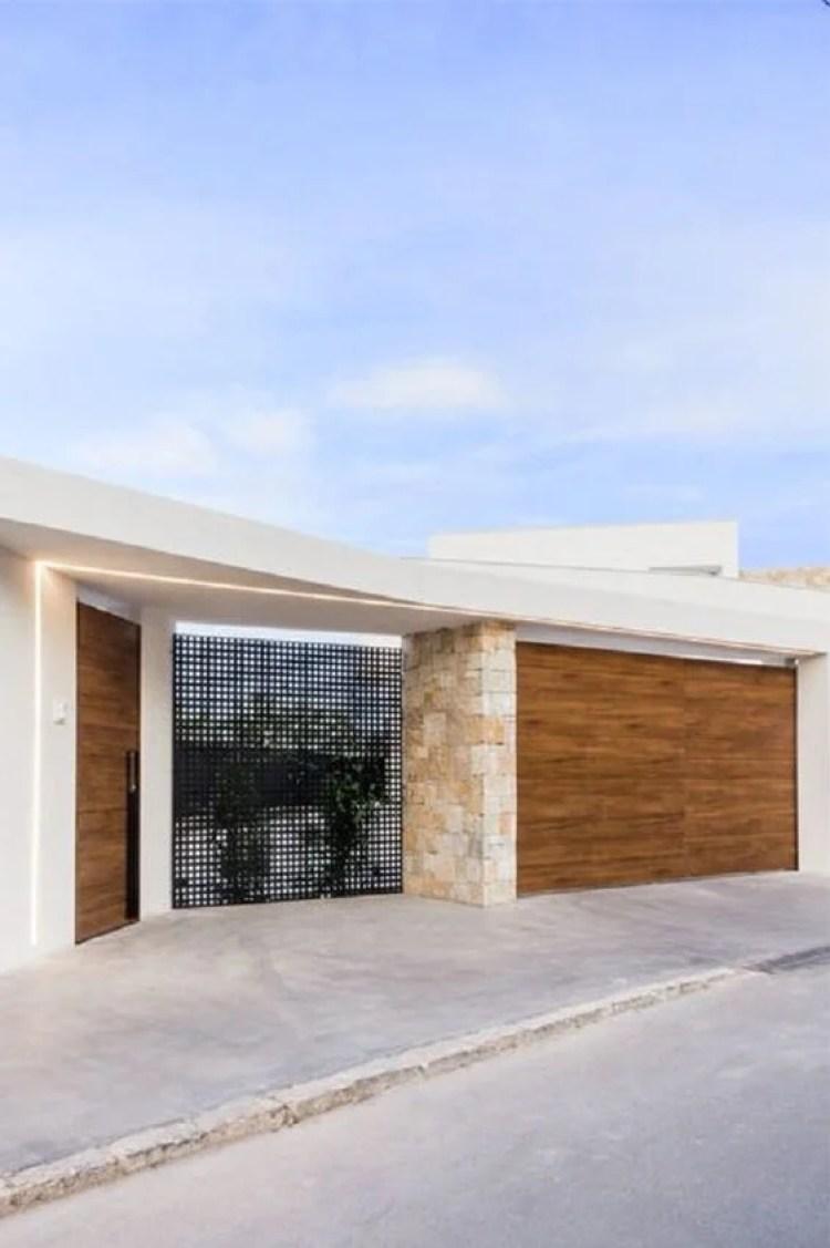 Portões de madeira e muro de pedra.