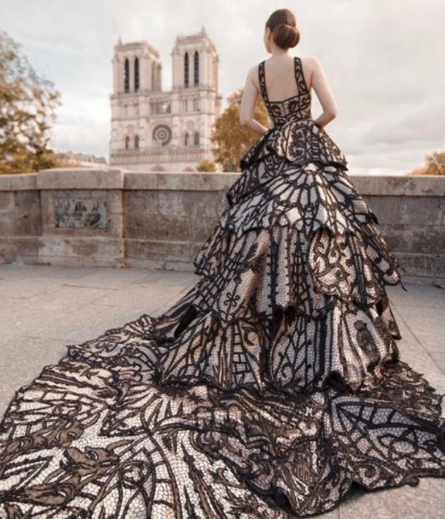 Modelo posando em Paris, de costas, com o vestido Catedral de Ivanildo Nunes, com Notre Dame ao fundo