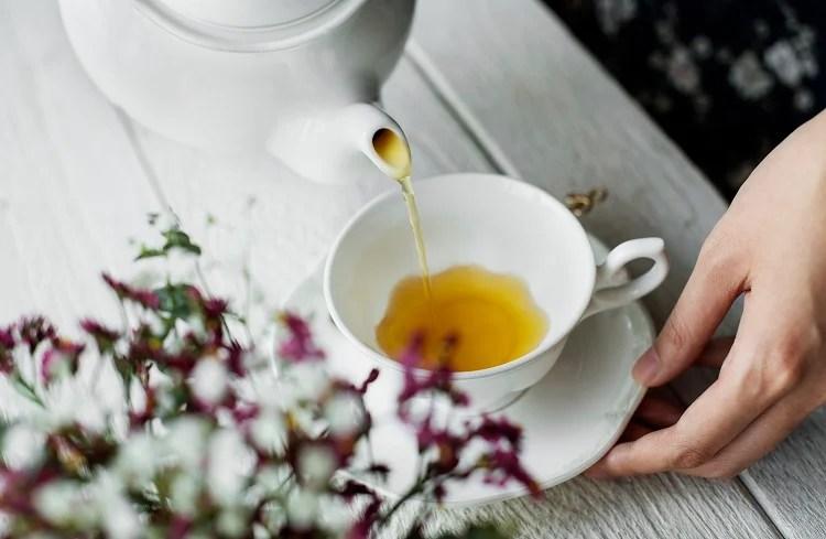 Mulher colocando chá de açafrão em uma xícara