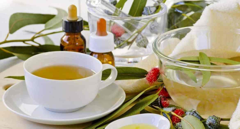 Mesa com chá, óleo e folhas de eucalipto