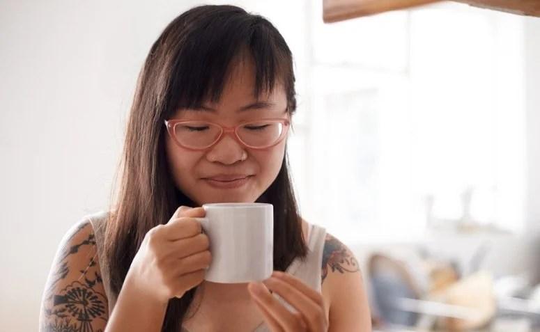 Mulher tomando chá de folhas de abacate em uma xícara branca
