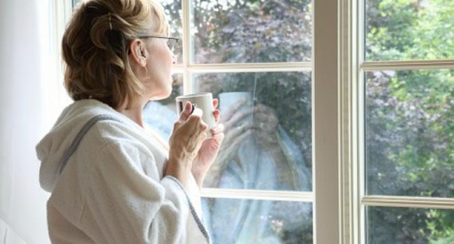 Mulher pensativa tomando chá e olhando pela janela