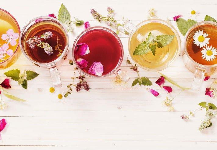 Superfície branca com xícaras de chá com diferentes plantas