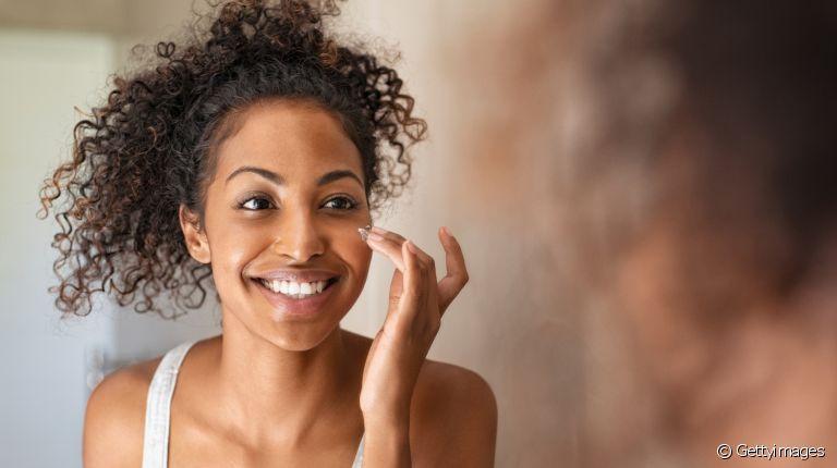 Mulher cuidando da pele e sorrindo frente ao espelho