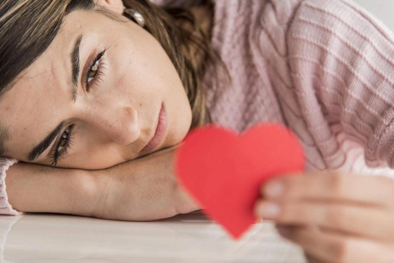 mulher triste com coração de papel na mão