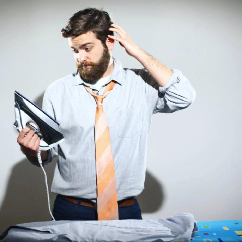 Homem de camisa e gravata olhando para ferro de passar com ar de preocupação e pensando
