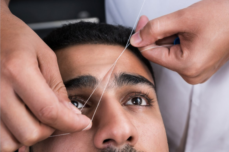 Homem recebendo procedimento de depilação egípcia nas sobrancelhas