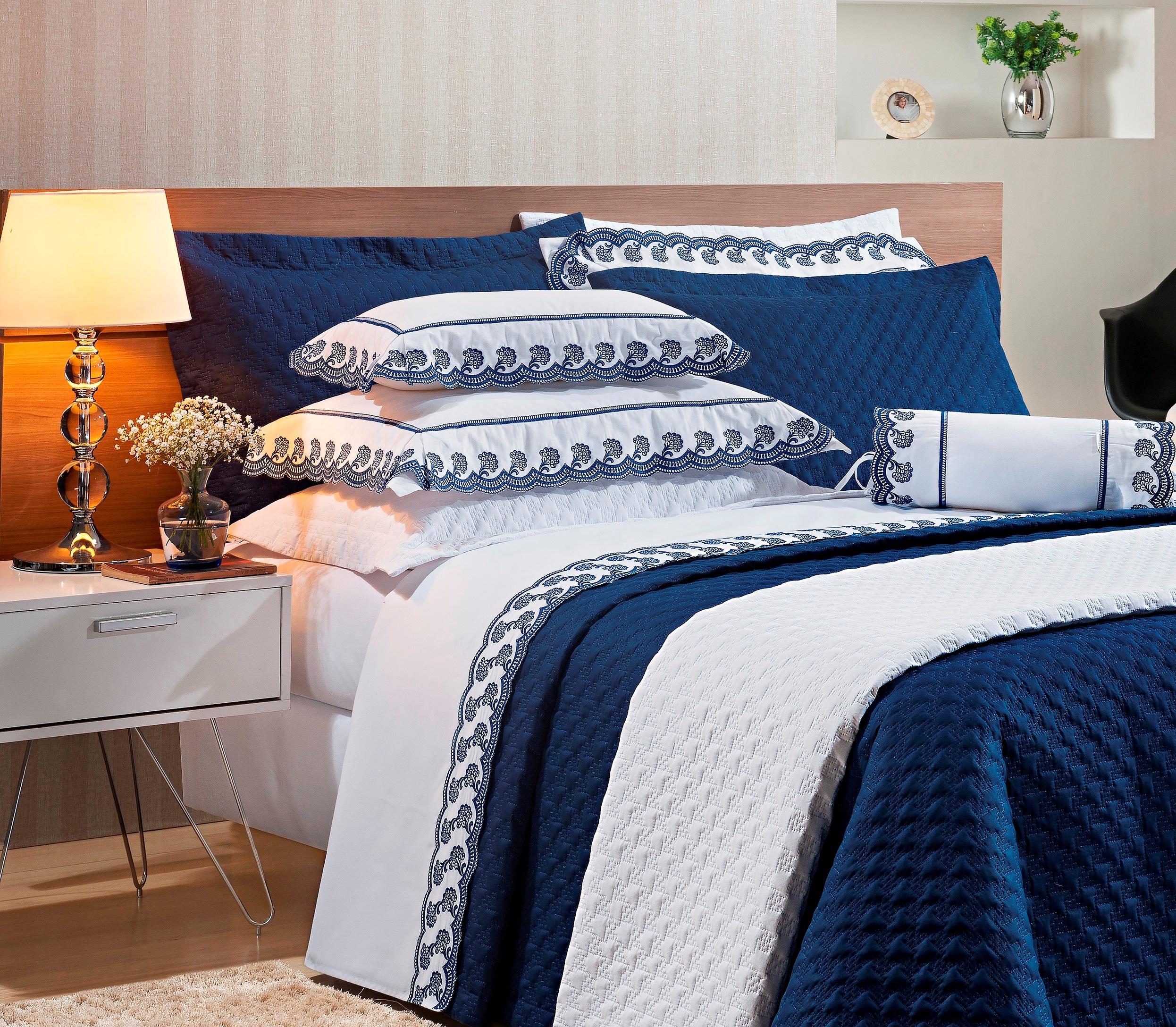 Roupa de cama azul e branca.