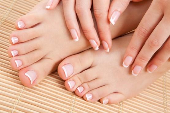Mãos e pés femininos sobrepostos demonstrando as unhas