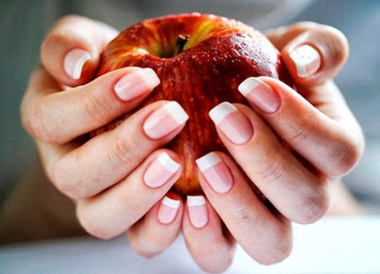 Mãos segurando uma maçã com foco para as unhas saudáveis