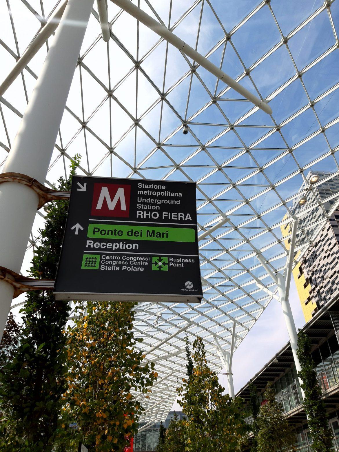 Entrada da feira do Salão de Móveis de Milão 2021 com corredor verde de árvores