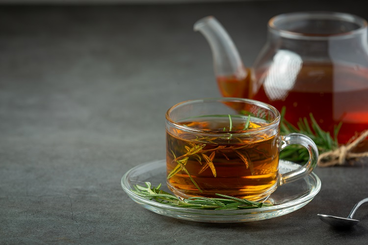 Foto de xícara de vidro com chá de alecrim