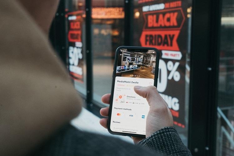 Foto de pessoa consultando preço de produto no celular