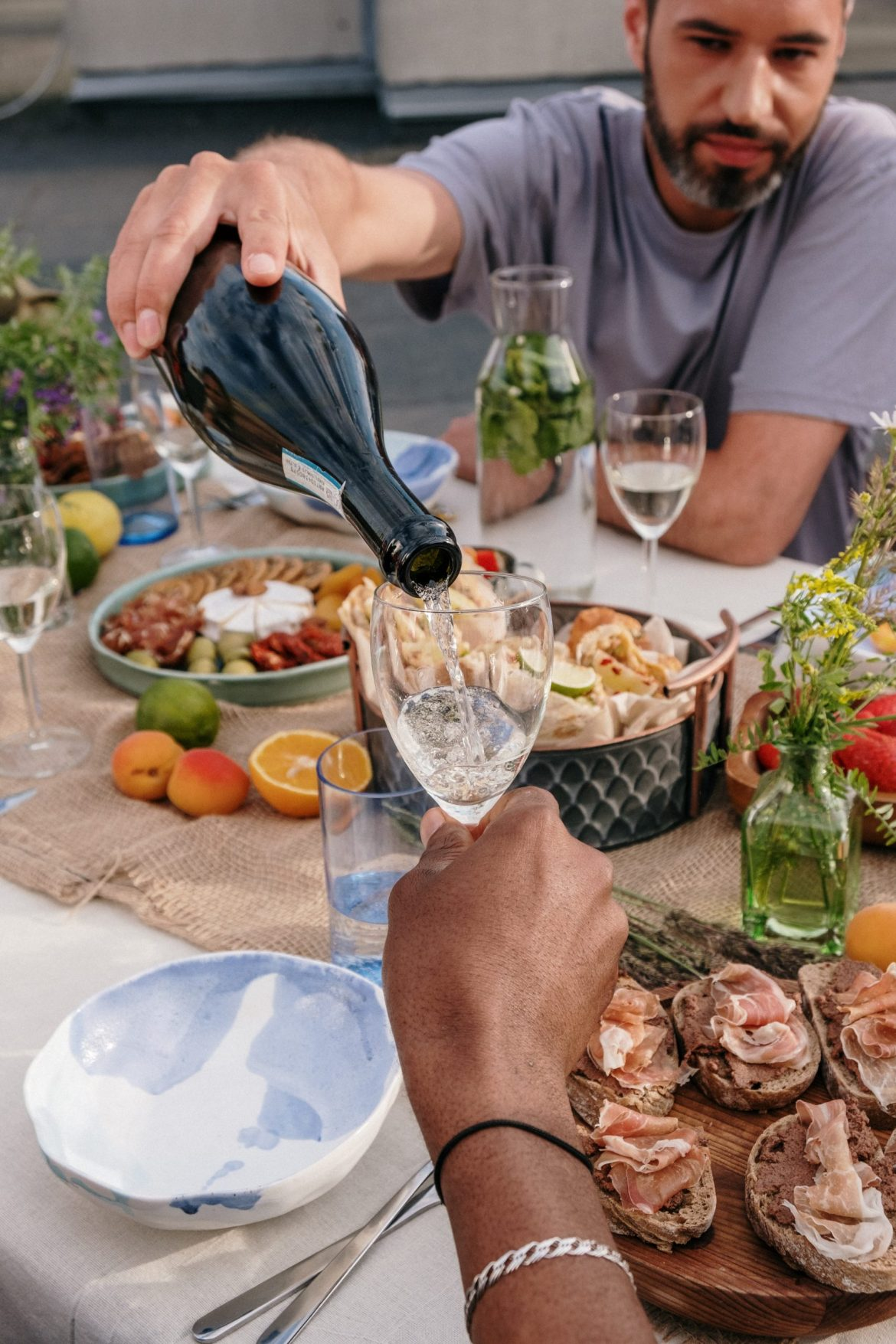 Foto com uma mesa de aperitivos com presento, queijos e duas pessoas bebendo vinho