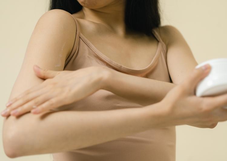 Foto de mulher massageando os braços. Auto drenagem linfática.
