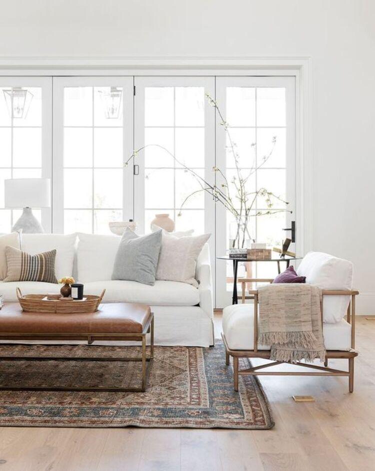 Sala com sofá e poltrona brancos.