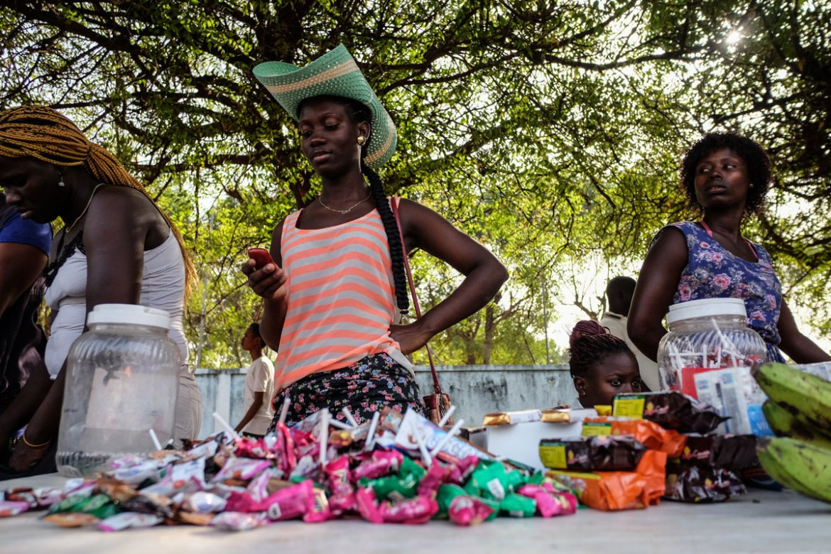 A woman selling sweets on the  a green cowboy hat sells candy on the sidelines of Bissau's carnival, wears a rather stunning green cowboy hat. [Ricci Shryock/Al Jazeera]