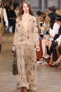 A model wears a long maxi dress on Chloe's fall 2015 runway. The 1970s inspired silhouettes of the show delivered hippie glamour.