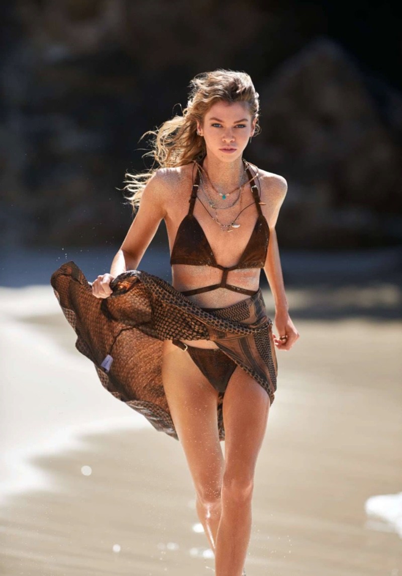 Stella models monokini with skirt while posing on the beach