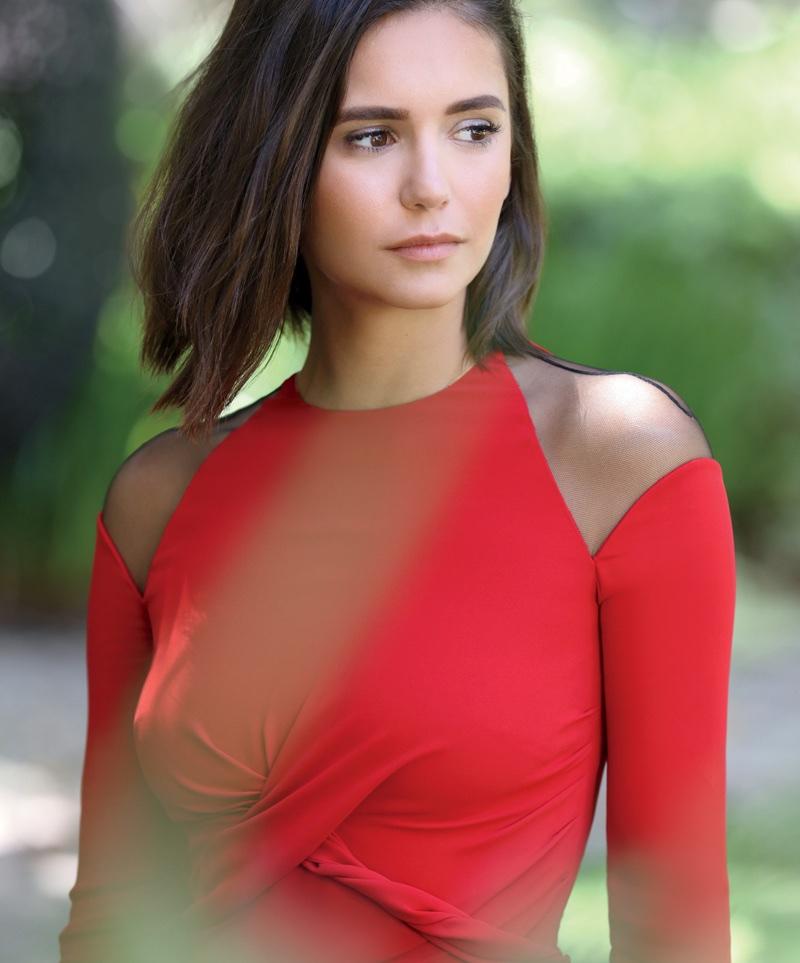 Nina Dobrev poses in red Versace open shoulder dress