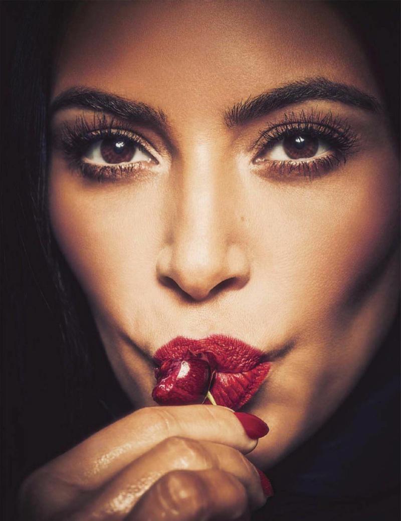 Kim Kardashian poses in bold scarlet lipstick with matching manicure
