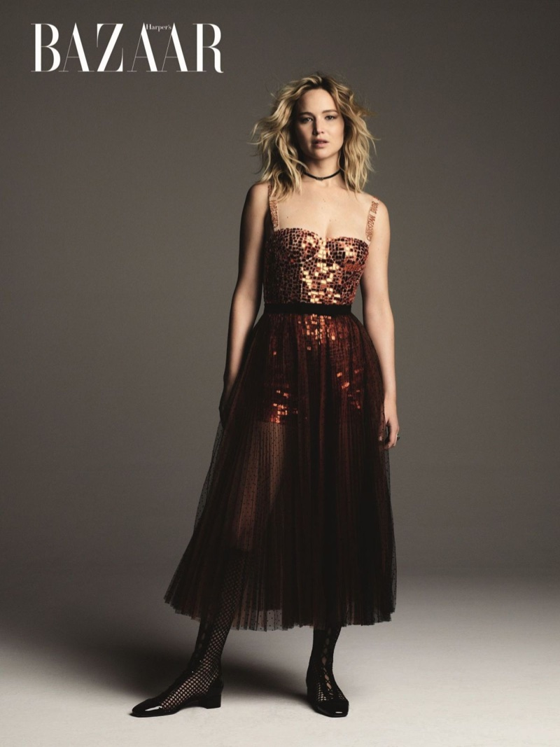 Actress Jennifer Lawrence poses in orange sequin Dior dress