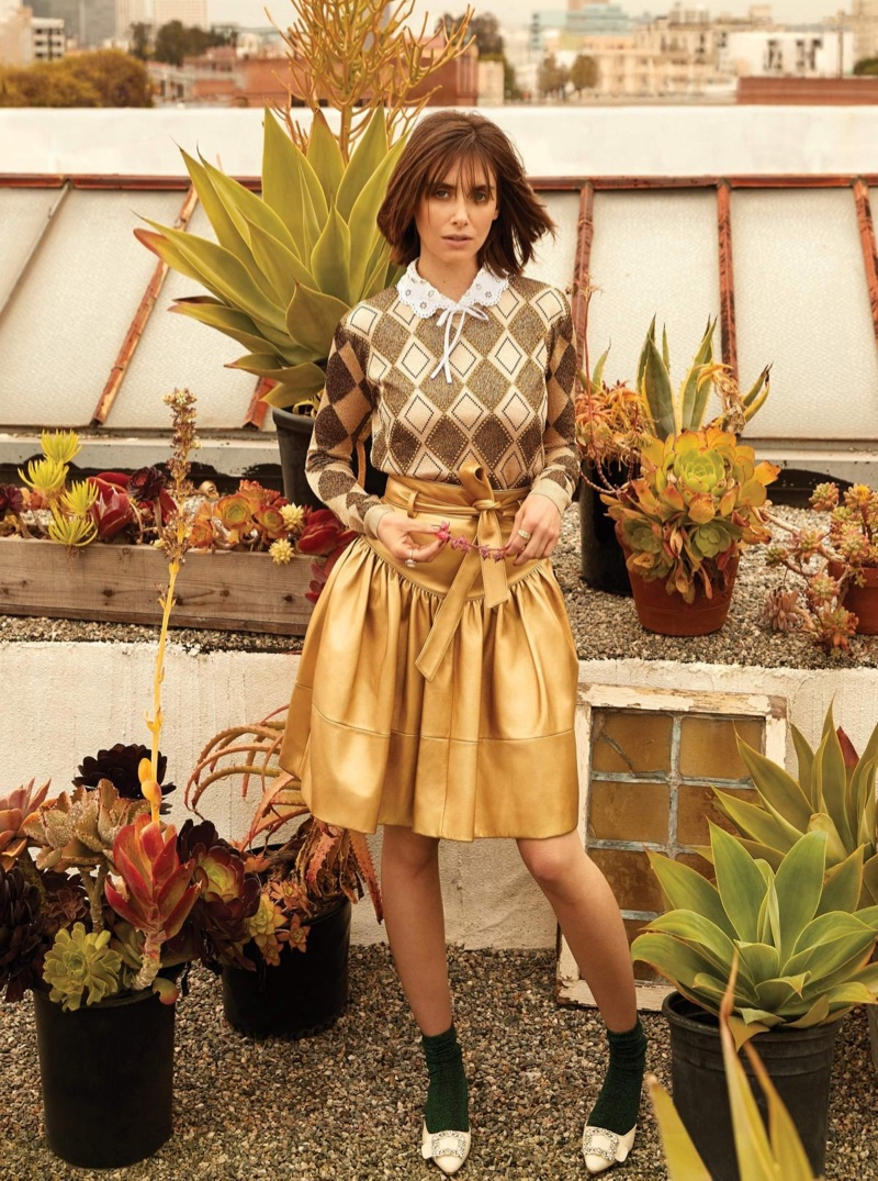Alison Brie poses in Miu Miu top, sweater and skirt with Manolo Blahnik shoes