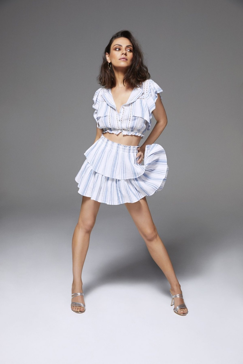 Actress Mila Kunis poses in a ruffled crop top and mini skirt