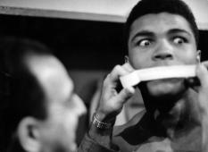 Heavyweight contender Ali and, 21 (later aka Muhammad Ali), getting his poetic mouth taped by trainer Angelo Dundee during his weigh-in before big fight w. Doug Jones.