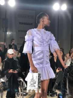 STARSICA FW18 LONDON FASHION WEEK a model in a purple tulle tiered dress holds a bag