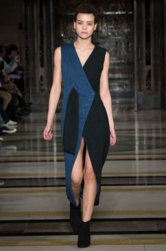 A model wears a denim and black wrap over dress on the runway for SOE Jakarta at london Fashion Week FW18
