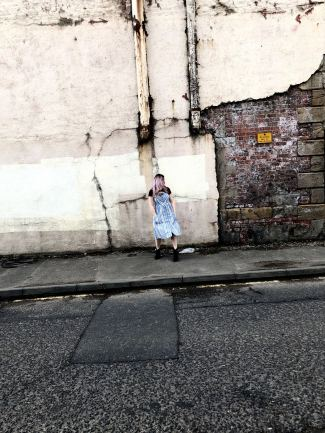 An image of pixie Tenenbaum wearing a blue and white striped Primark Summer dress with a black tee underneath and cowboy boots against a white wall