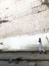 An image of pixie Tenenbaum walking along a street wearing a blue and white striped Primark Summer dress with a black tee underneath and cowboy boots against a white wall