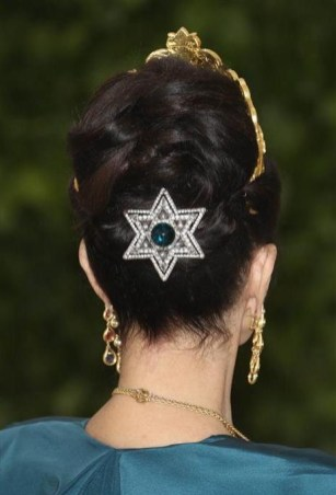 Rear view of lynda Carter's beauty and hair look at the 2018 met gala, complemented with an emerald star hair clip