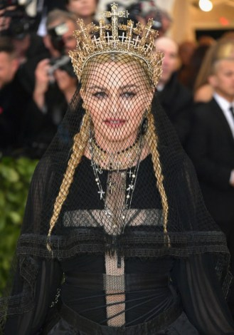 Madonna wearing all black and a widows lace veil with crown on the red carpet for the 2018 met gala