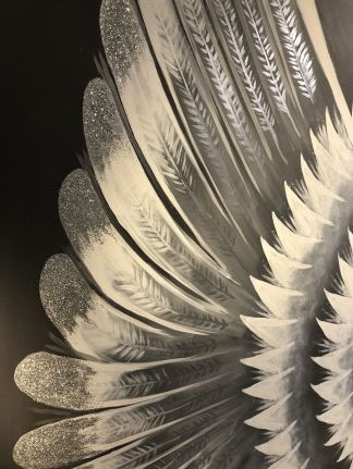 Close up of Angel wings painted on a dark grey feature wall in the new Novellus Aesthetics clinic room at 1 Benton Terrace in Jesmond. Glitter tipped wings lit up by a cinema type floor lamp featuring the words Novellus newcastle and #Apocalips. taken for Fashion Voyeur blog