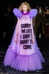 "a model in the Viktor & Rolf Spring 2019 Couture runway show in Paris featuring lots of tulle dresses bearing slogans, this one says ""sorry I'm Late I Didn't Want To Come"""