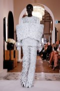 An image of a runway model at the Balmain couture Spring 2019 show wearing a trouser suit with bangles and wrap detailing covering the middle and pinning the arms to the body